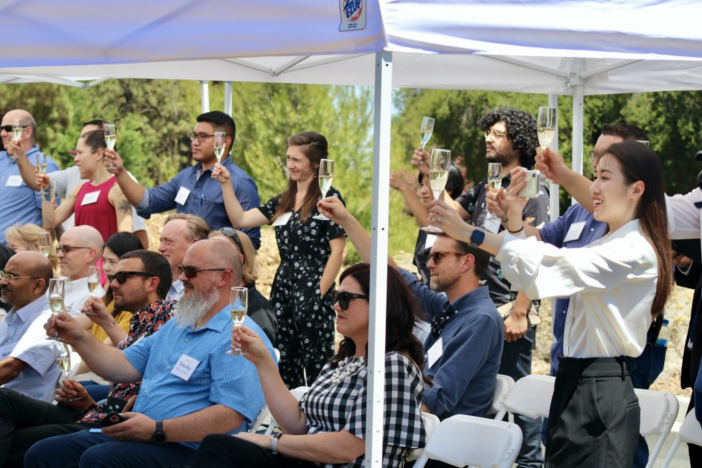 Guests toasting with champagne at the Coffee Center's dedication ceremony